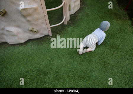 Baby crawling on grass Banque D'Images