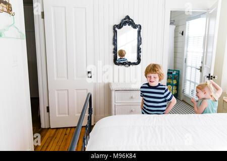 Deux enfants jouant à côté de lit blanc en blanc accueil Banque D'Images