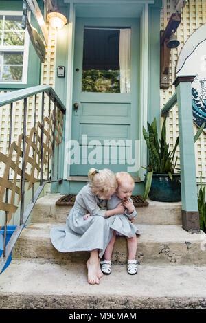 Fille et bébé assis dehors sur les marches Banque D'Images