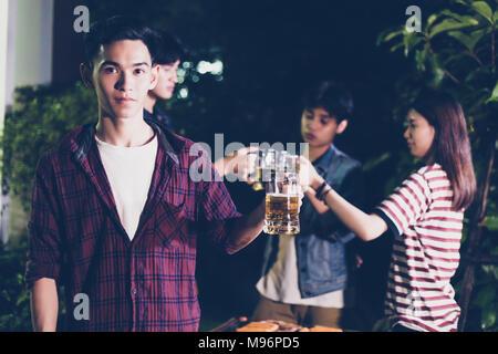Groupe d'amis asiatiques ayant piscine jardin barbecue rire avec bière sans alcool Boissons sur nuit Banque D'Images