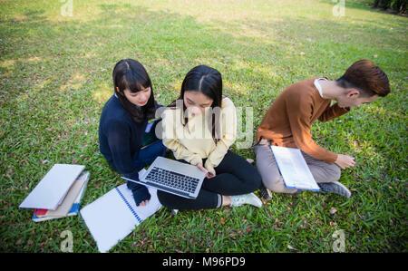 Groupe d'étudiants universitaires asian assis sur le travail de l'herbe verte et de la lecture à l'extérieur ensemble dans un parc Banque D'Images