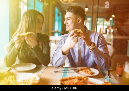 La photo en gros du jeune couple enjoying in pizza, avoir du plaisir ensemble. Le consumérisme, de l'alimentation, style de concept Banque D'Images