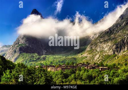 Le village de Chiappera, dans la haute vallée de la Maira à Piedmont, le rock, surmontée d 538, partiellement enrobée depuis les nuages. Banque D'Images