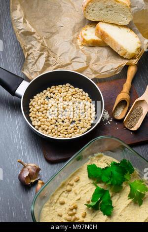 L'hoummos ou houmous, apéritif en une purée de pois chiches avec tahini, citron, ail, huile d'olive, le persil, le cumin et noix de cèdre sur table en bois. Style de vie sain et bien manger concept Banque D'Images