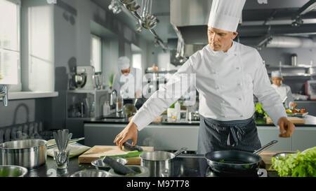 Le Restaurant Le Chef prend et met le poisson sur une poêle chaude. Il travaille dans une cuisine moderne. Banque D'Images