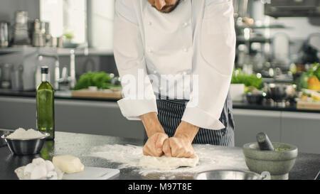 Chef du célèbre restaurant Boulanger pétrit la pâte dans un cadre moderne à la cuisine. Banque D'Images