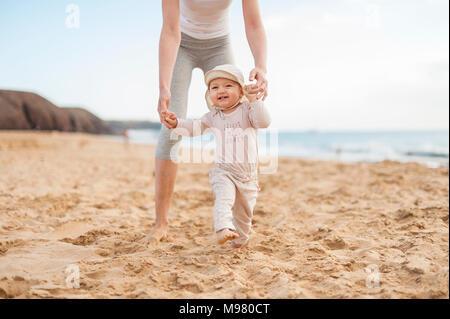 Aider la mère petite fille marchant sur la plage Banque D'Images