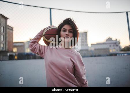 Portrait of young woman holding basket-ball extérieur