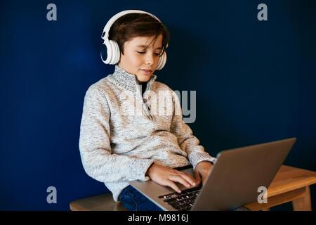 Garçon assis sur un banc portant des écouteurs et using laptop Banque D'Images