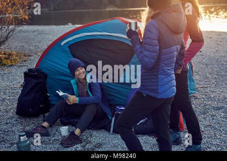 Groupe de randonneurs du camping au lac au coucher du soleil Banque D'Images