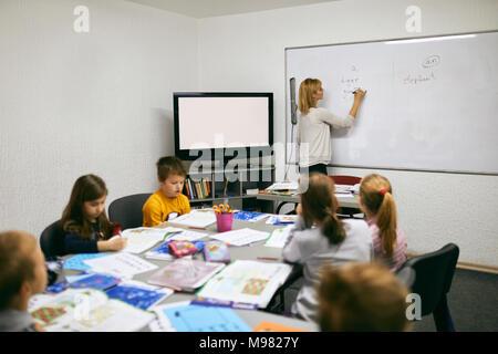 L'écriture de l'enseignant sur le tableau blanc dans la classe Banque D'Images