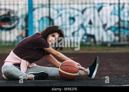 Jeune femme avec le basket-ball s'étend sur la cour en plein air Banque D'Images