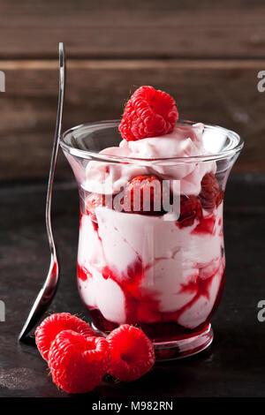 Verre de peu de crème fouettée, fraises et sauce aux fraises Banque D'Images