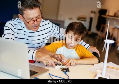 Le père et le fils de l'assemblage d'un kit de construction avec ordinateur portable et modèle d'éolienne Banque D'Images