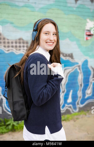 Allemagne, Berlin, portrait of laughing young woman with backpack listening music with headphones Banque D'Images