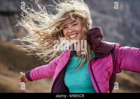 Happy young woman appuyé contre le vent dans les montagnes Banque D'Images
