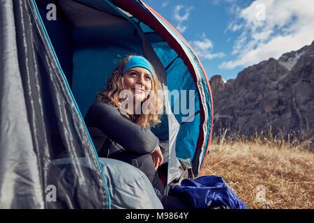 Smiling young woman sitting in tente dans les montagnes Banque D'Images