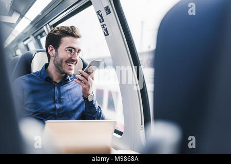 Happy businessman in train using cell phone Banque D'Images