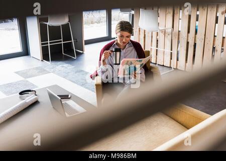 Jeune femme assise dans un fauteuil à lire des documents Banque D'Images