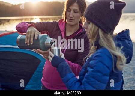 Deux femmes avec boisson chaude du camping au lac