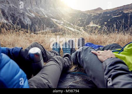 Les jambes de couple sitting in tente dans les montagnes Banque D'Images