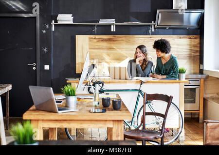 Deux jeunes femmes using laptop in modern office Banque D'Images