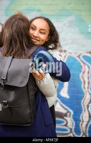 Allemagne, Berlin, portrait of happy young woman hugging her friend Banque D'Images