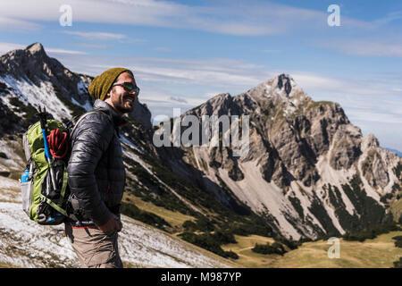 Autriche, Tyrol, smiling young man en randonnée dans les montagnes Banque D'Images