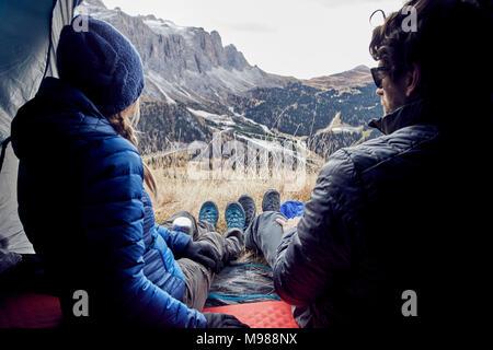 Couple sitting in tente dans les montagnes à la vue à Banque D'Images