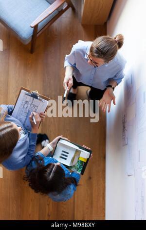 Groupe de femmes architectes ayant une réunion, vu de directement au-dessus Banque D'Images