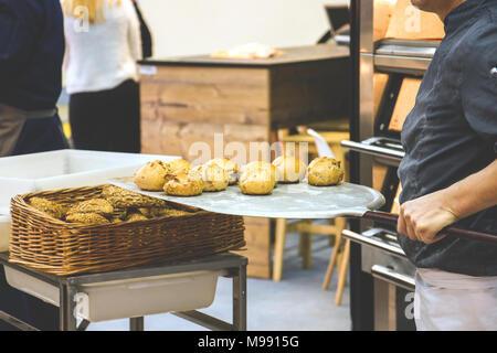 Baker holding freshly baked scones dans four fork Banque D'Images