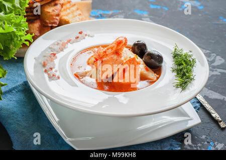 Soupe de poisson française Bouillabaisse aux fruits de mer, filet de saumon, crevettes, saveur riche, délicieux dîner dans un beau plat blanc. Close up. Banque D'Images