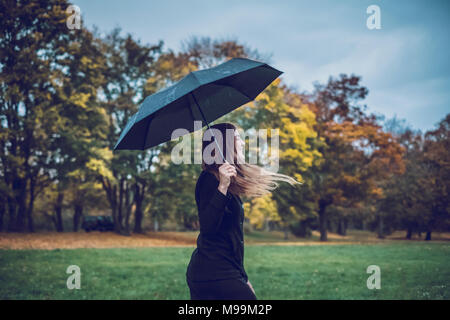 Happy young woman with umbrella walking in autumnal park Banque D'Images