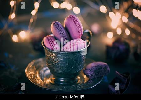 Des petits macarons sur une coupe de métal de l'argent avec de l'effet bokeh voyants sur le fond en bois. Focus sélectif. Spase copie Banque D'Images