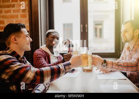 Beaux mecs sont tintement des bouteilles de bière, looking at camera et souriant tout en vous reposant à pub Banque D'Images