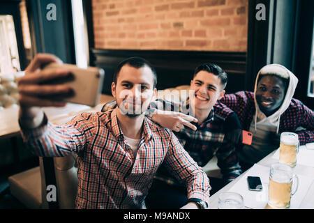 Les gens, les loisirs, l'amitié, de la technologie et concept bachelor party - happy friends mâle et boire de la bière à selfies bar ou pub Banque D'Images