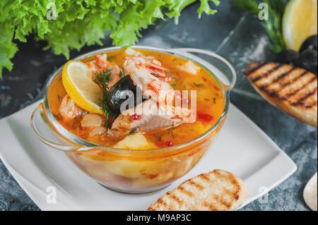 Soupe de poisson française Bouillabaisse aux fruits de mer, filet de saumon, crevettes avec une saveur riche, avec des croûtons. Délicieux dîner dans une plaque de verre transparent. C Banque D'Images
