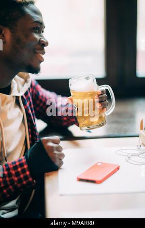 African American beau est de boire une bière tout en vous reposant à pub Banque D'Images