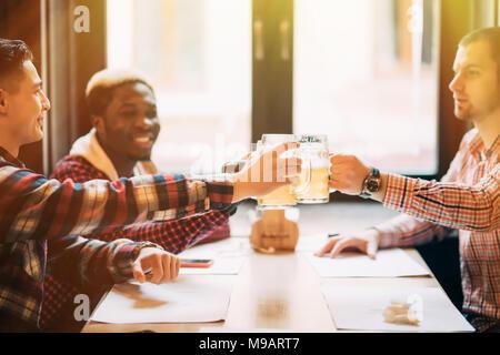 Les gens, les hommes, les loisirs, l'amitié et de fête concept - heureux amis boire une bière et clinking glasses au bar ou au pub Banque D'Images