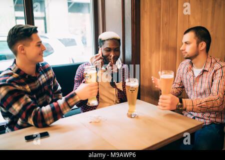 Deux hommes amis dans le bar sont la consommation de bière et de communiquer alors que l'on parle sur le téléphone et demander de garder le silence. Banque D'Images