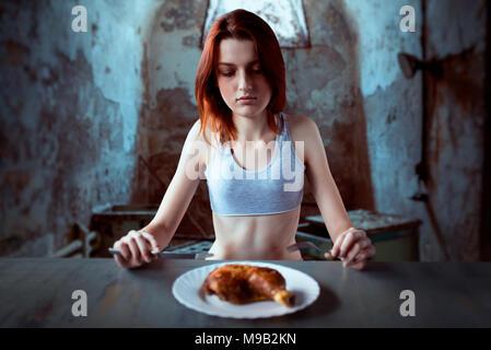 Femme contre la plaque avec de la nourriture, de l'absence d'appétit Banque D'Images