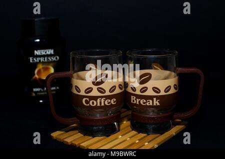 Nei,la Serbie, le 13 mars 2018:deux verres inhabituelle avec design café disant pause café avec nescafé bocal en verre flou en arrière-plan sur noir, studio Banque D'Images