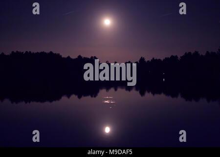 L'offre super lune reflétée dans un lac sur le ciel nocturne d'un violet foncé avec des silhouettes d'arbres dans la région de Westford, Massachusetts, USA. Banque D'Images