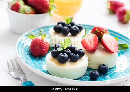 Mini cheesecake aux fraises et bleuets sur plaque bleue, vue rapprochée. Syrniki, crêpes de fromage cottage Banque D'Images