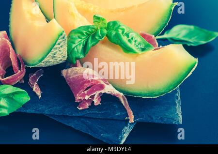 Concept de l'alimentation italienne au melon et prosciutto sur fond sombre. Apéritif traditionnel l'antipasto. Focus sélectif. Banque D'Images