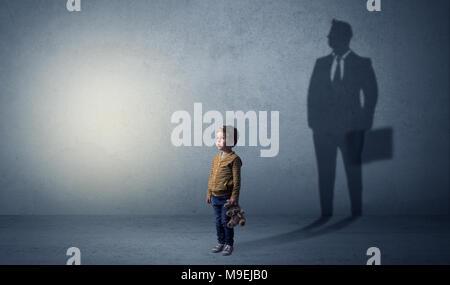 Petit garçon imaginer qu'il sera homme d'affaires et illustrant son avenir dans une grande ombre Banque D'Images