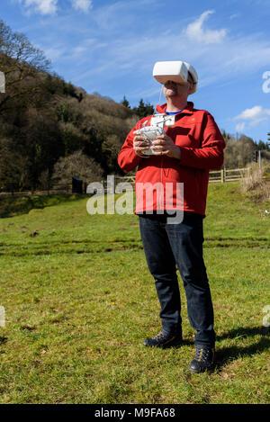 Vallée de la Wye, Monmouthshire, UK. 25 mars 2018: l'homme dans les vêtements de randonnée, aux commandes d'un drone quadcopter en utilisant des lunettes FPV Banque D'Images