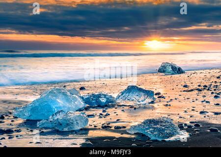 Blocs de glace à la dérive sur la plage du Diamant, au coucher du soleil, Jokulsarlon, Islande