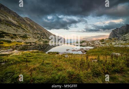 Lac de montagne au-dessus de la cascade Skok au coucher du soleil. Vallée Mlynicka, Hautes Tatra, la Slovaquie. Banque D'Images