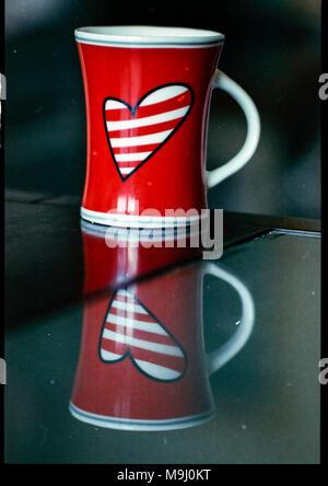 Numérisation à partir de film couleur imparfaite vieille caméra analogique avec la poussière et les rayures. avec cadre noir de négatif. Coffee cup avec coeur Banque D'Images